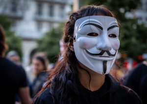 A man wears a Guy Fawkes mask whilst protesting