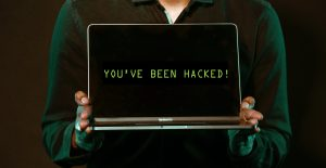 A man holds up a laptop that says 'you've been hacked' on the screen